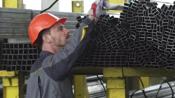 Zpětná záběr mužského úložiště pracovního uspořádání kovových trubek na polici