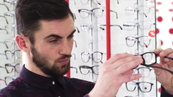 Pohledný muž zkoumání brýle v obchodě Optometristé