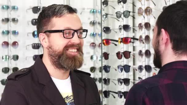 Reifer männlicher Kunde im Gespräch mit dem Optiker bei der Wahl einer neuen Brille