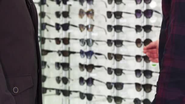 Oříznutý snímek muž potřásl rukou s optometristy v obchodě brýlí
