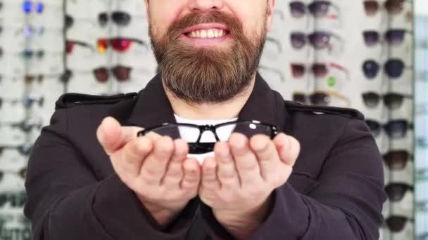 Oříznout záběr vousatý muž s úsměvem podal brýle k fotoaparátu