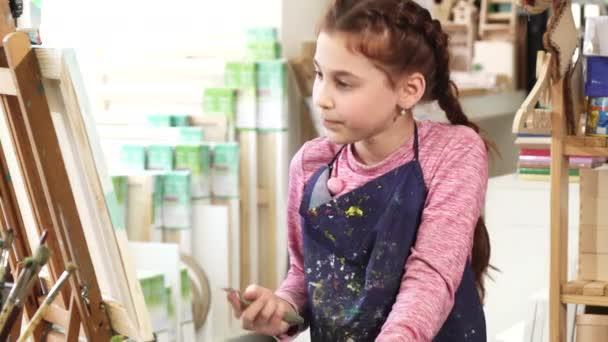 Szép kislány festés a festőállvány, olajfesték segítségével a művészeti stúdió