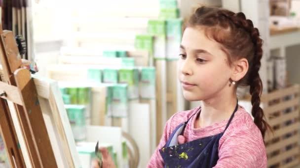 Egy aranyos kislány iskolában festőállvány festés közelről