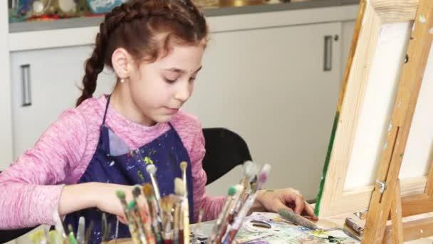 kleines glückliches schönes Mädchen lächelt in die Kamera im Kunstatelier
