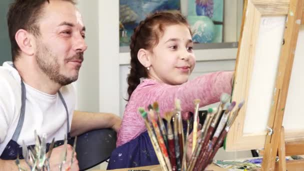 Proud father watching his lovely daughter painting a picture
