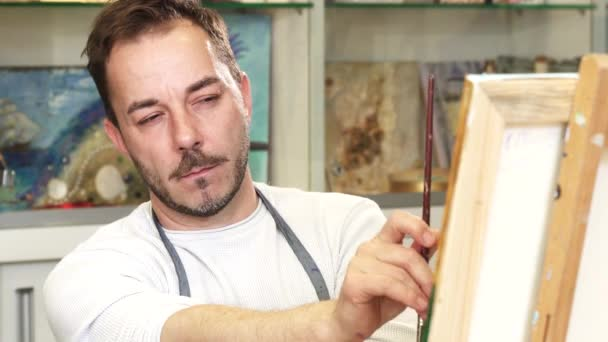 Professional artist concentrating over his painting