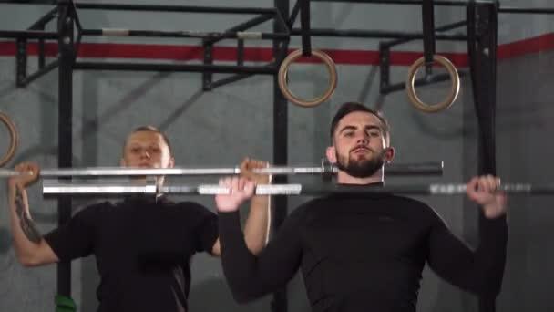 Mužské crossfit atletů se zahřívá v posilovně zvedat činky