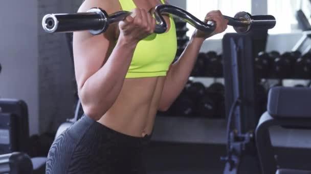 Oříznuté záběr atletické ženy dělají biceps kadeře v tělocvičně