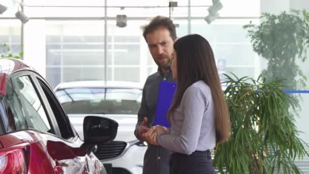 Professional car dealer opening car door for his female client