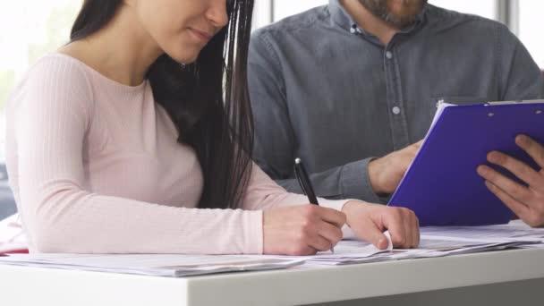 Oříznutý snímek ženy podepisování dokumentů s prodejcem na autosalonu