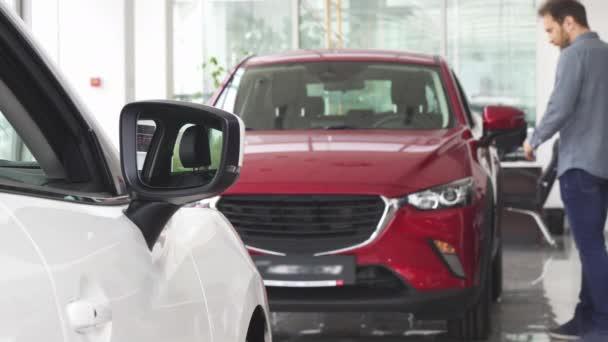 Mature man choosing a new car at the dealership salon