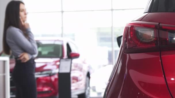 Female customer choosing a new car at the dealership salon