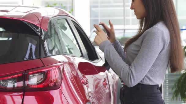 Cropped shot of a woman using her smart phone standing near her car