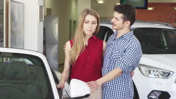 Loving couple examining a new convertible for sale at the dealership