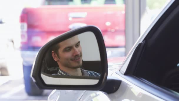 Zblízka boční zrcátka automobilu, šťastný muž řidič s úsměvem