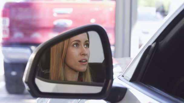 Beautiful female driver smiling to the camera in the side mirror