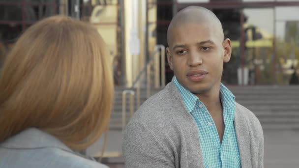 Handsome cheerful African American man talking to a friend outdoors