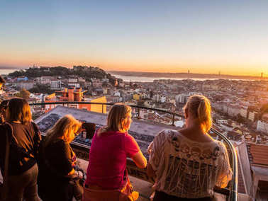 LISBON, PORTUGAL - NOVEMBER 19, 2017: Tourists at Belvedere of Our Lady of Hill viewpoint looking at cityscape of Lisbon at sunset