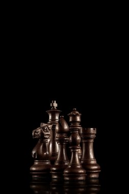 Chess set. Strategy and leadership concept; black wooden chess figures standing together as a family ready for game against dark background.