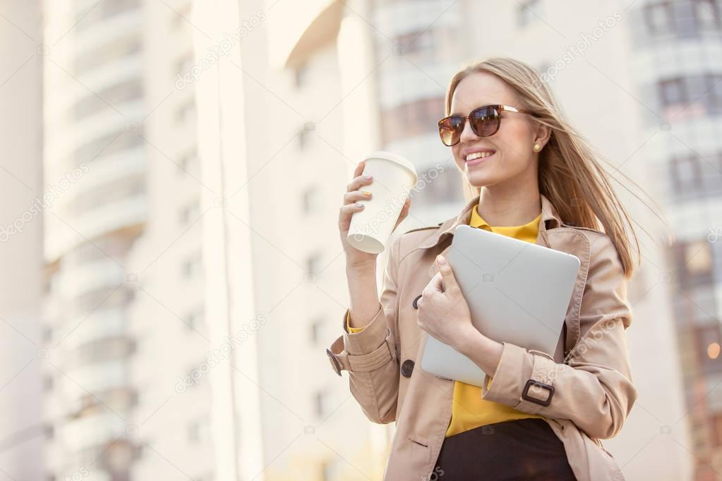 Business morning. Beautiful young businesswoman with a disposable coffee cup, drinking coffee, and holding tablet in her hands against urban city background.