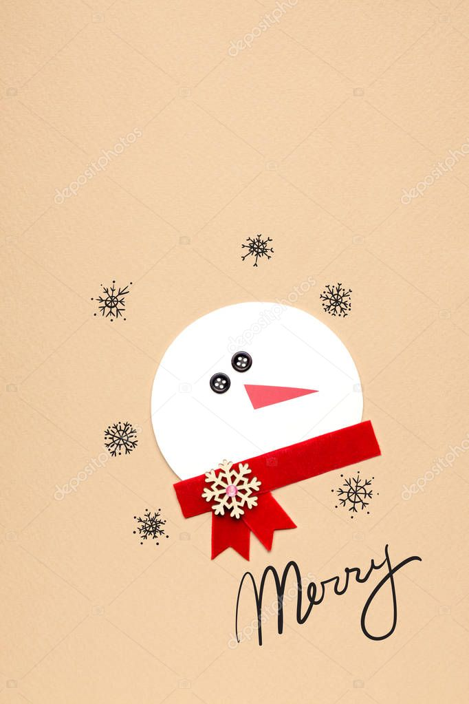 Merry christmas. Creative photo of a snowman mad of paper on brown background.