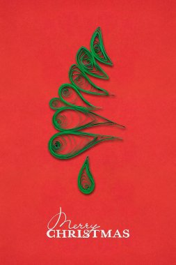 Magic tree. Creative concept photo of a christmas tree made of paper on red background.