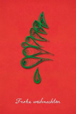 Magic tree. Creative concept photo of a christmas tree made of paper on red background. Frohe Weihnachten.