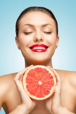 A creative portrait of a beautiful smiling woman squeezing a red grapefruit in her hands. stock vector