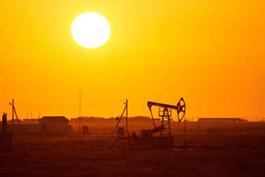 Pumpjack on sunset background.A pumpjack is the overground drive for a reciprocating piston pump in an oil well.The arrangement is commonly used for onshore wells producing little oil. Pumpjacks are common in oil-rich areas. stock vector