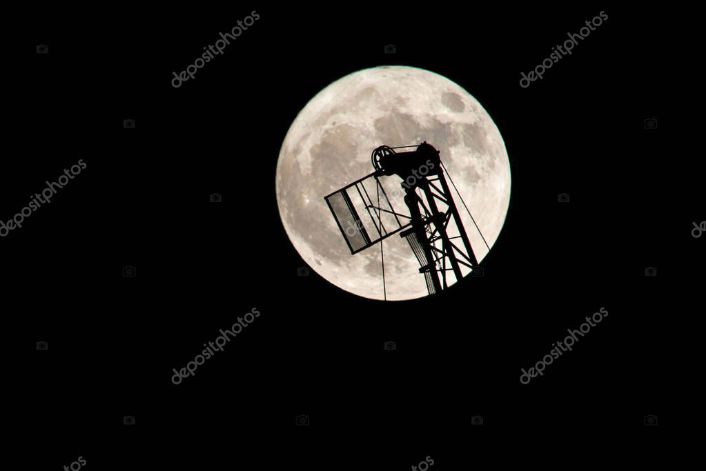 Construction crane against the background of the full moon. A super moon is a full moon or a new moon that approximately coincides with the closest distance that the Moon reaches to Earth in its elliptic orbit.