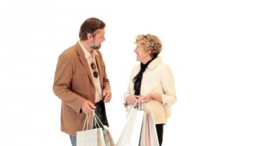 Mature couple shoppers showing their bags