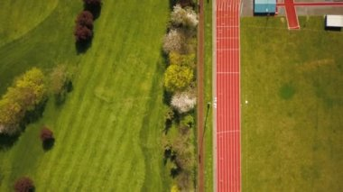 Running track. Aerial drone view looking vertically down and following the lines of a running track flanked by green fields of the field area and adjoining golf course.