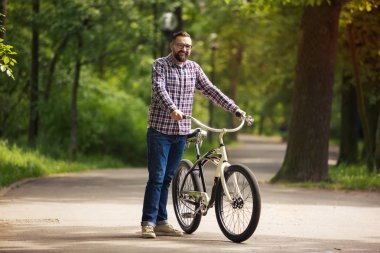 Young happy man standing with bike at park