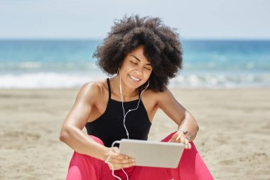 Happy afro american woman on beach listening music on tablet