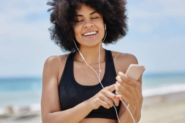 Afro american woman listening audiobook on mobile smiling