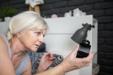 Senior woman holding alarm clock checking out time