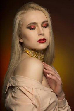 Attractive young woman with perfect makeup in red color and gold