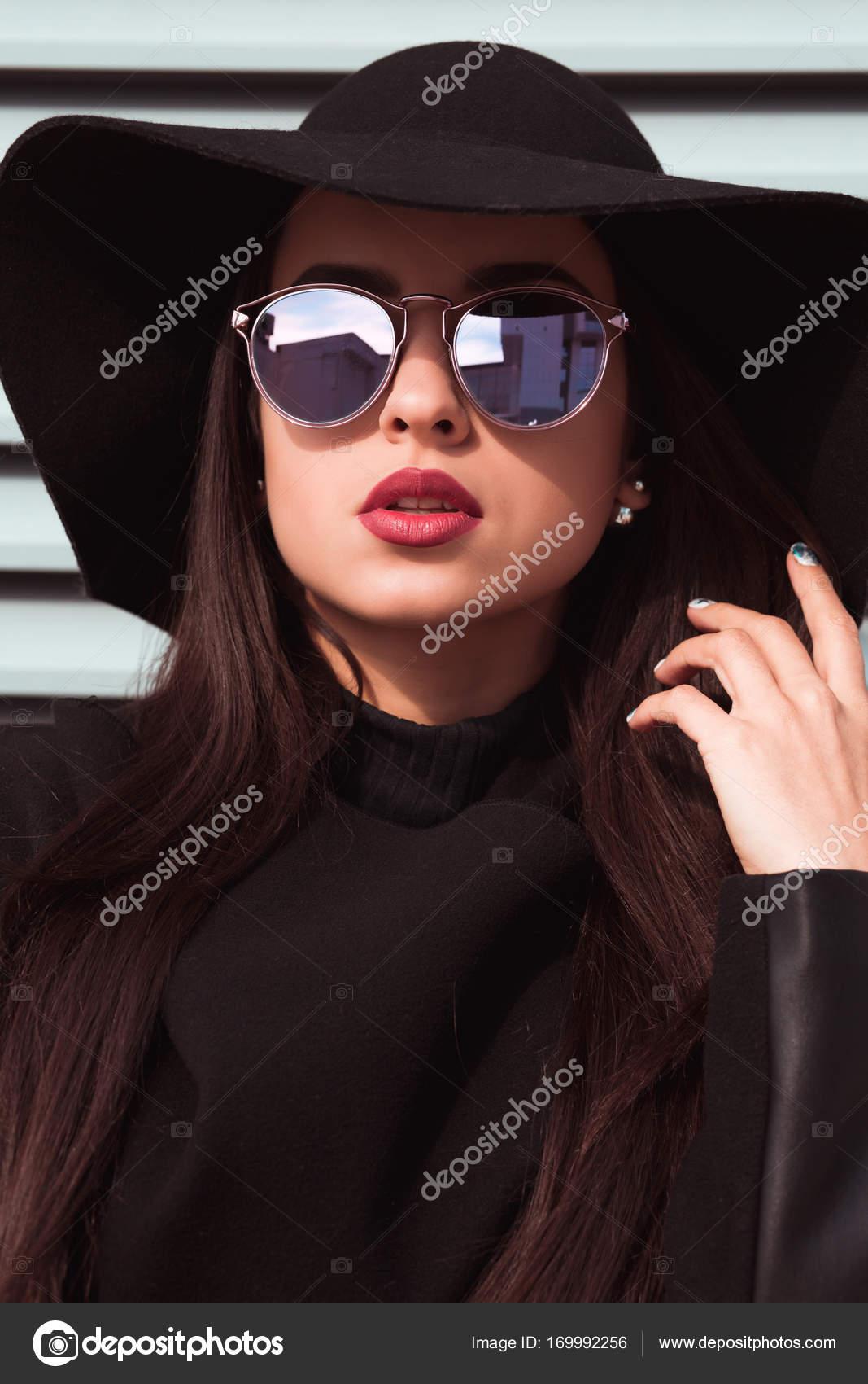 a19e0deb23 Closeup retrato de joven atractiva viste sombrero y gafas de sol. Mujer  posando en el fondo de persianas en día soleado - mujeres con sombrero y  lentes ...