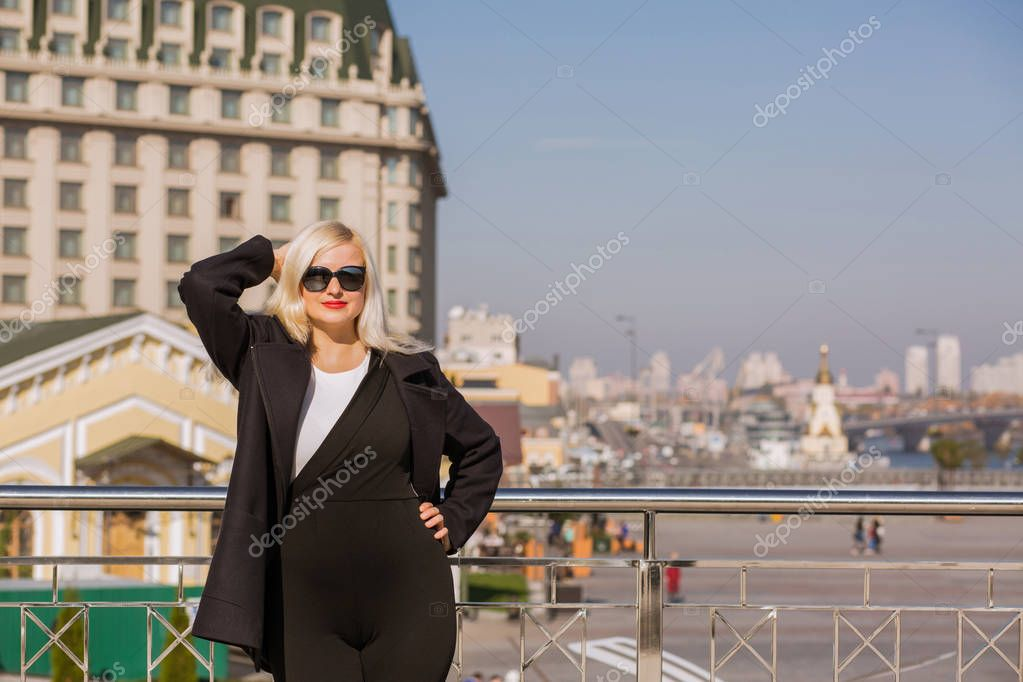 Wonderful blonde model posing in black coat, wears sunglasses on