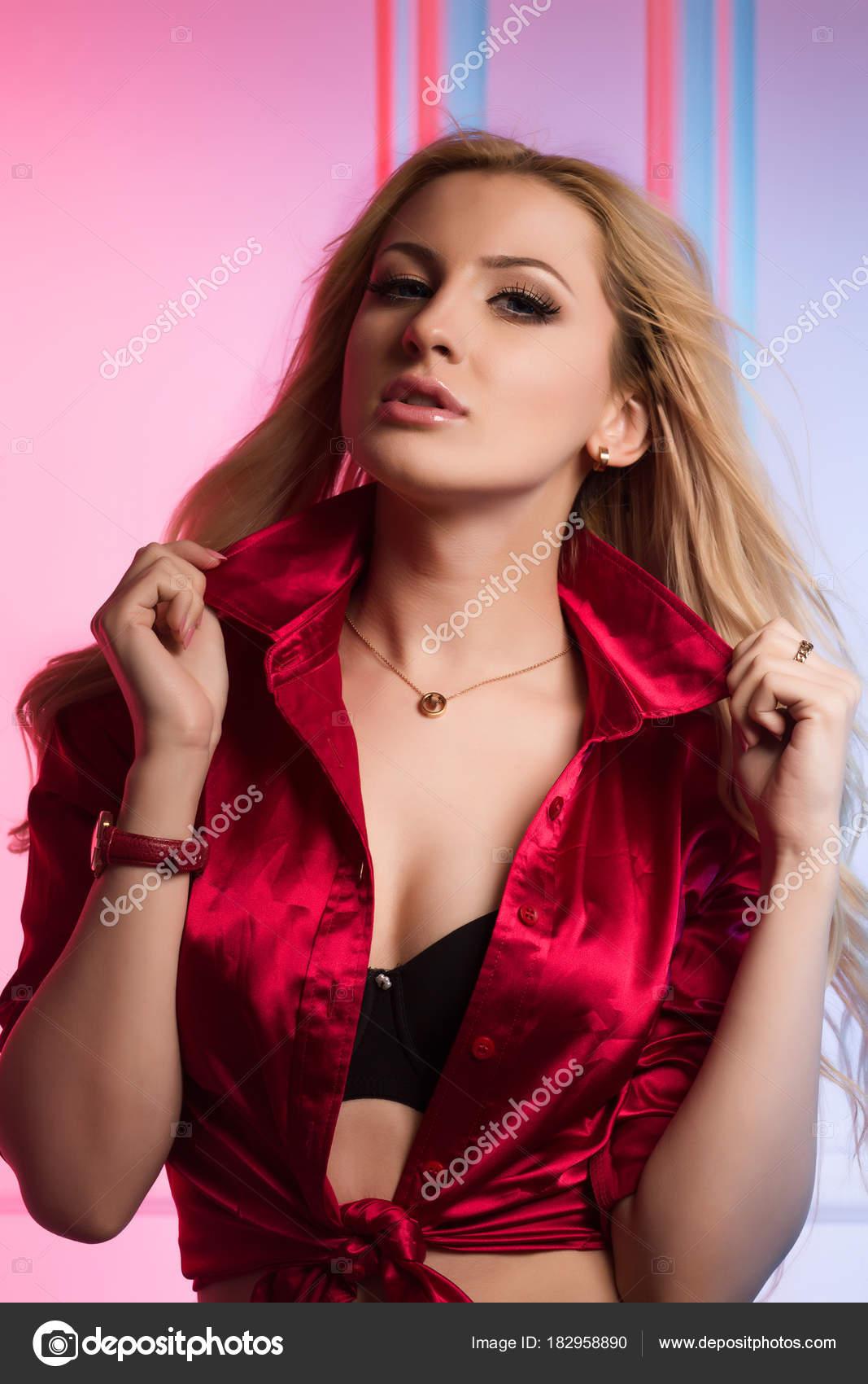448beba8b16e Γοητευτική νεαρή γυναίκα με σπαστά μαλλιά που φοράει μετάξι κόκκινη μπλούζα