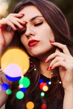 Closeup portrait of sensual brunette woman posing with colorful