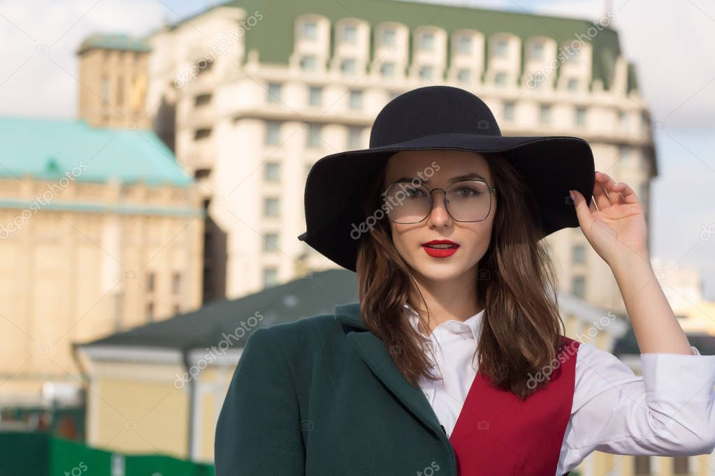 Street portrait of wonderful young lady posing at the city. Woma