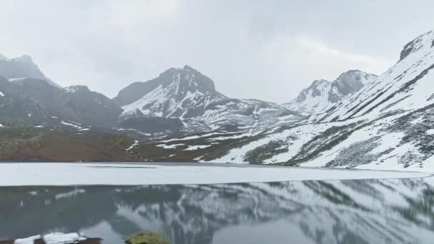 Csúszik a tükör felett Ice Lake, havas komor csúcsok tükrözik a sima víz, Nepál