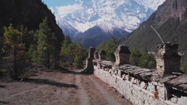 Forest trekking path near buddhist Mani wall lead to snow mountain Annapurna II
