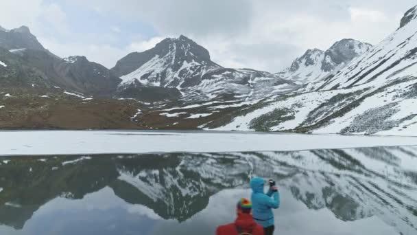 Sliding above Ice Lake, mirror reflection of snow peak on water, tourists, Nepal