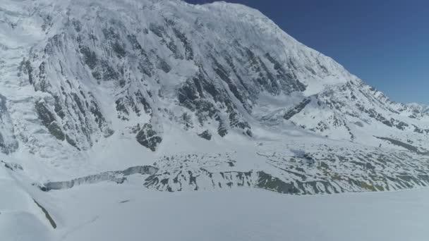 Ledové jezero Tilicho, majestátní tyčící se zasněžené Tilicho Peak, modrá obloha, lehké mraky