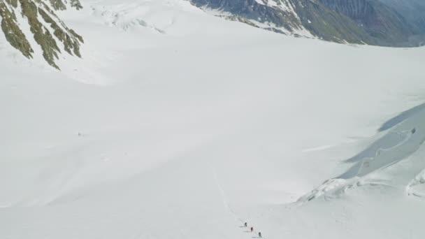 Alpine Expedition klettert über breiten Schneehang, sonnige malerische Hochlandlandschaft