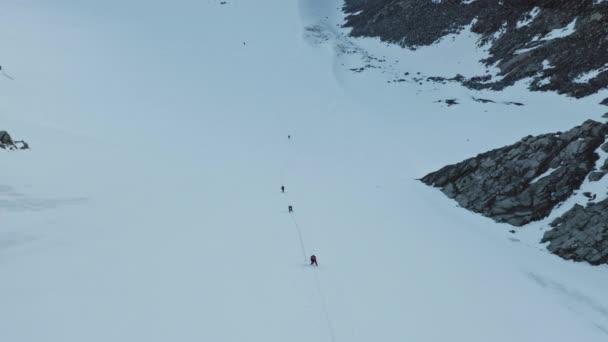 Overhead flight, people climbs up over mountain snow slope, mountaineering