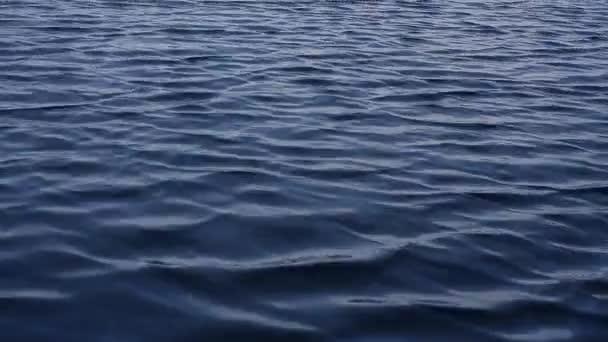A szél kék hullámokat kelt egy kis tó felszínén. Közelről. Ukrajna, Luganszk régió.