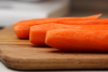 Peeled carrots on wooden chopping board.